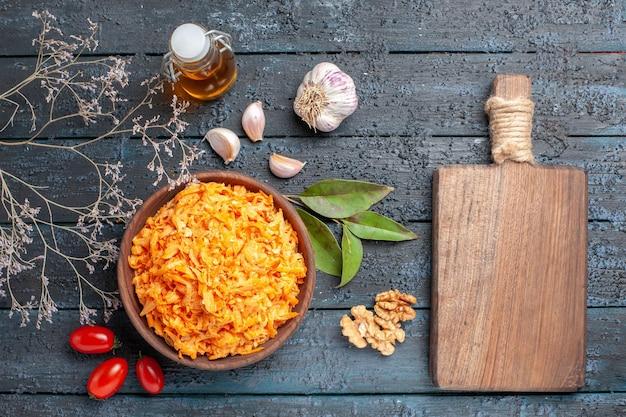 Bovenaanzicht geraspte wortelsalade met walnoten en knoflook op de donkere achtergrond gezondheidsdieet oranje kleur rijpe salade