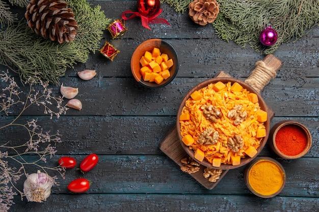 Bovenaanzicht geraspte wortelsalade met walnoten en kruiderijen op een donker bureau gezondheidssalade notenkleur voedseldieet