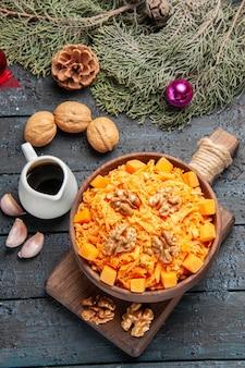 Bovenaanzicht geraspte wortelsalade met walnoten op donker bureau gezondheidssalade dieet noten kleur voedsel