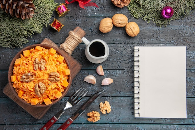 Bovenaanzicht geraspte wortelsalade met walnoten op donkerblauw bureau gezondheid salade dieet noten kleur voedsel