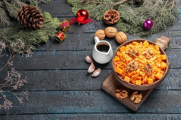 Bovenaanzicht geraspte wortelsalade met walnoten op donkere bureau gezondheidssalade dieet notenkleur