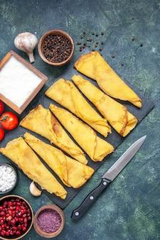 Bovenaanzicht gerolde pannenkoeken bekleed met tomaten op donkere achtergrond deeg hotcake kleur maaltijd taart vlees gebak taart zoet Gratis Foto