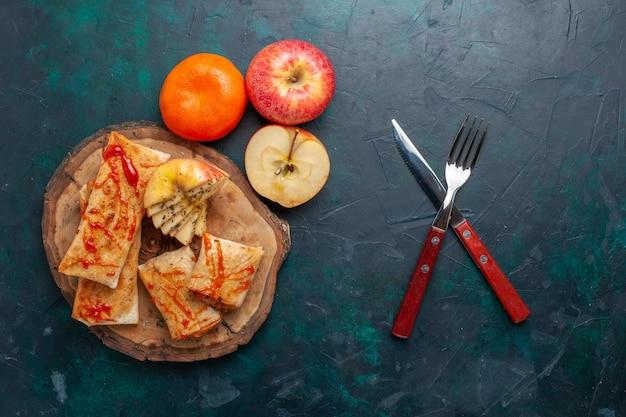 Bovenaanzicht gerolde pita deeg gesneden met saus en fruit op het donkerblauwe bureau