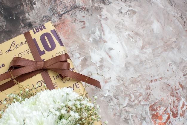 Bovenaanzicht geschenk witte bloemen op grijze tafel