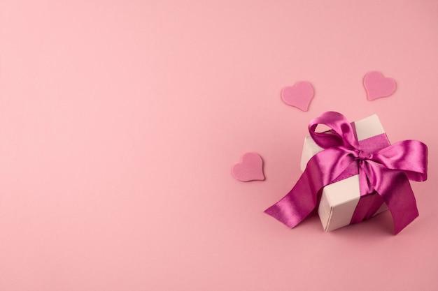 Bovenaanzicht geschenkdoos met feestelijke satijnen strik en drie harten op een zacht roze achtergrond met kopie ruimte