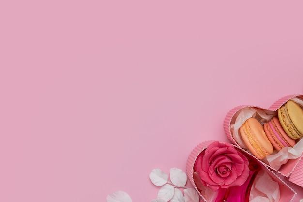 Bovenaanzicht geschenkdozen hartvorm met bloemen en bitterkoekjes op een roze achtergrond met kopie ruimte valentijnsdag datum of partij concept