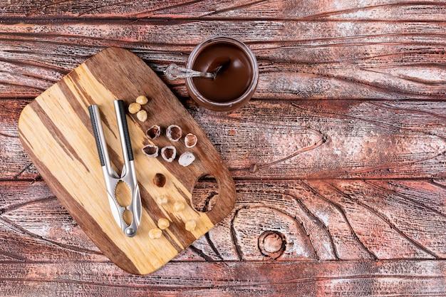 Bovenaanzicht geschilde en schoongemaakte hazelnoten met cacaopasta en notekrakers op houten tafel.