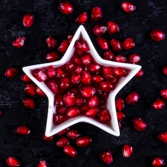 Bovenaanzicht geschilde granaatappel in de vorm van een ster op een zwarte muur