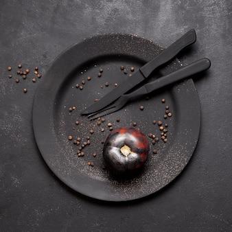 Bovenaanzicht geschilderd zwarte gebakken tomaten en kruiden