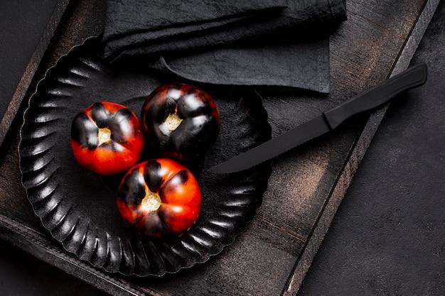 Bovenaanzicht geschilderd zwarte gebakken tomaten op plaat met bestek