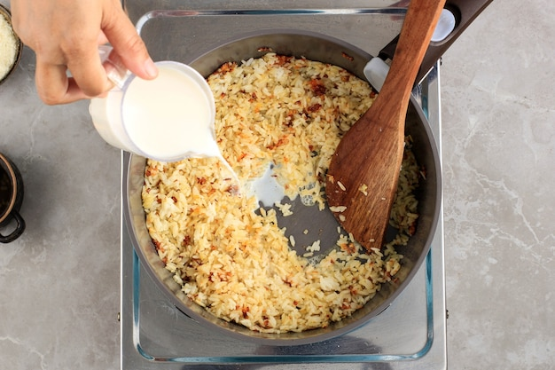 Bovenaanzicht geselecteerde focus vrouwelijke hand giet melk in de pan met rijst ingrediënten, thuis koken proces maken rijst recept met ui, knoflook en andere kruiden