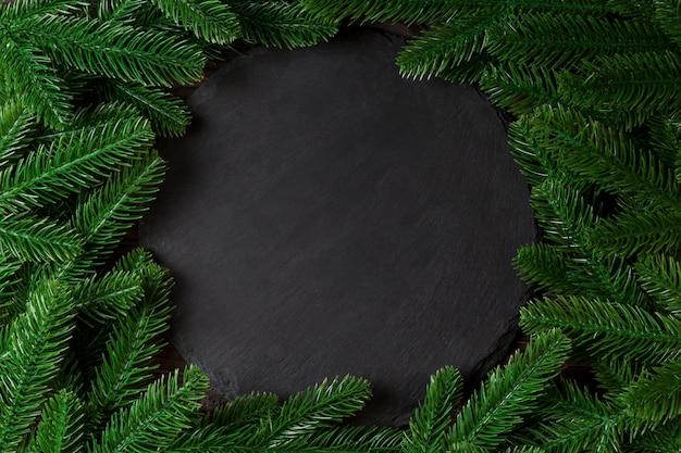 Bovenaanzicht geserveerd plaat met groene fir tree takken.