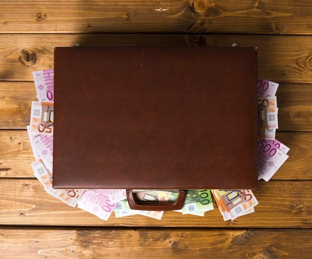Bovenaanzicht gesloten houten koffer met euro