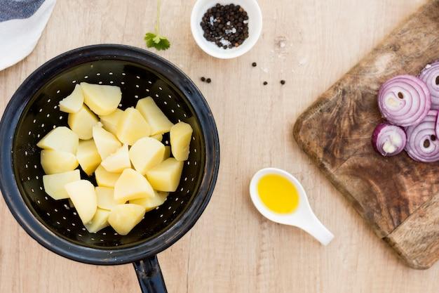 Bovenaanzicht gesneden aardappelen en uien