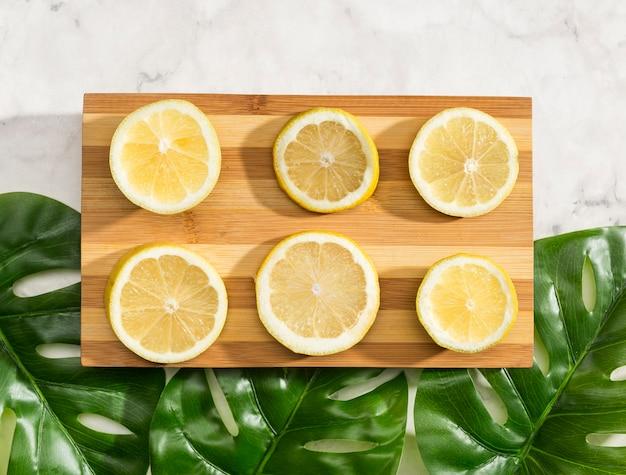 Bovenaanzicht gesneden citroenen op houten bord