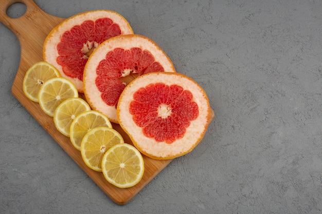 Bovenaanzicht gesneden citrusvruchten frisse, zachte, sappige grapefruits en citroenen op de grijze vloer