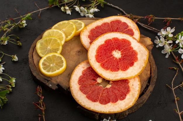 Bovenaanzicht gesneden citrusvruchten grapefruits en citroenen zacht rijp op het bruine bureau en donker