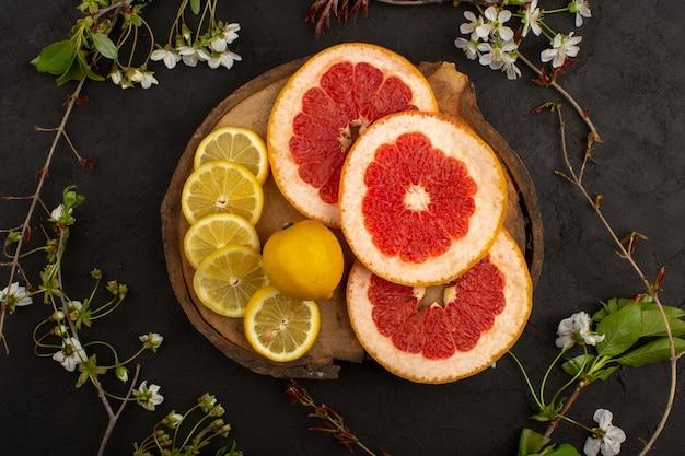 Bovenaanzicht gesneden citrusvruchten verse zachte citroenen en grapefruits op het bruine bureau en de donkere vloer