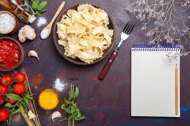 Bovenaanzicht gesneden deeg met tomatensaus en tomaten op de donkere achtergrond maaltijd deeg eten pasta diner