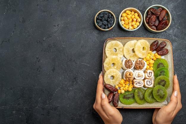 Bovenaanzicht gesneden gedroogde vruchten ananasringen en kiwi's op een grijs bureau droog fruit rozijnen zoet vitamine zure gezondheid