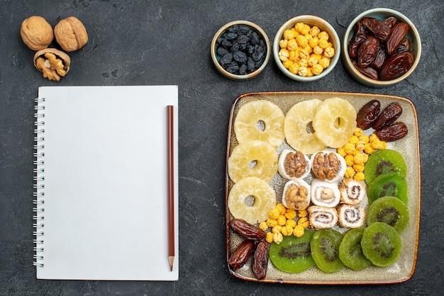 Bovenaanzicht gesneden gedroogde vruchten ananasringen en kiwi's op grijs bureau droog fruit rozijnen zoet vitamine zure gezondheid