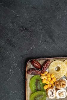 Bovenaanzicht gesneden gedroogde vruchten ananasringen en kiwi's op grijze achtergrond droge vruchten rozijnen zoetzure vitamine gezondheid