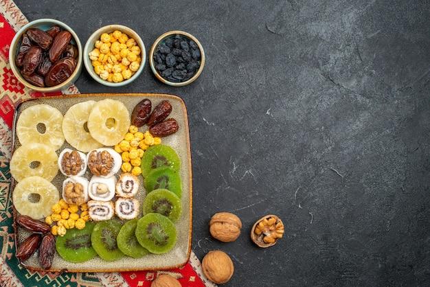 Bovenaanzicht gesneden gedroogde vruchten ananasringen en kiwi's op grijze achtergrond droog fruit rozijnen zoet vitamine zure gezondheid
