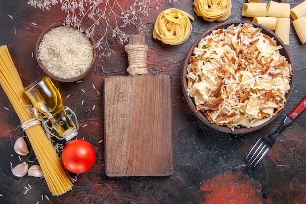 Bovenaanzicht gesneden gekookt deeg met rijst op het donkere oppervlak pastaschoteldeeg donker