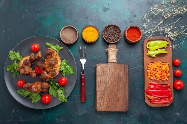 Bovenaanzicht gesneden gekookt vlees met kerstomaatjes in plaat en met kruiden op blauwe achtergrond