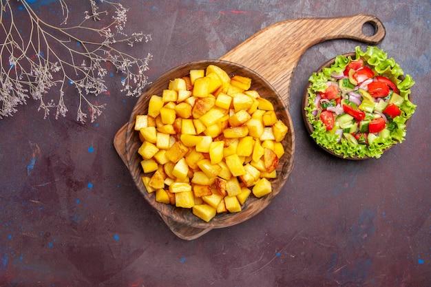 Bovenaanzicht gesneden gekookte aardappelen met groentesalade op het donker