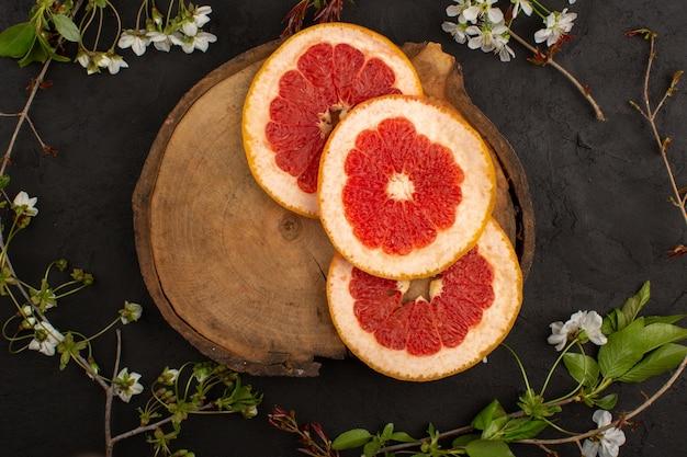 Bovenaanzicht gesneden grapefruit sappige rijpe mellow op de donkere achtergrond