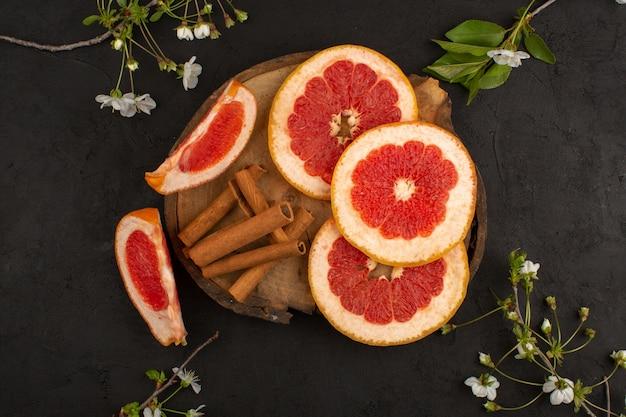 Bovenaanzicht gesneden grapefruit verse zachte sappige rijp samen met kaneel op het bruine bureau en grijze vloer