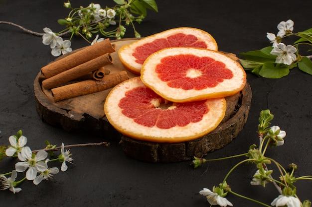 Bovenaanzicht gesneden grapefruit verse zachte sappige samen met kaneel op de donkere vloer