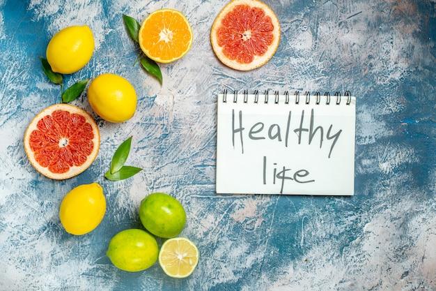 Bovenaanzicht gesneden grapefruits citroenen gezond leven geschreven op kladblok op blauw wit oppervlak