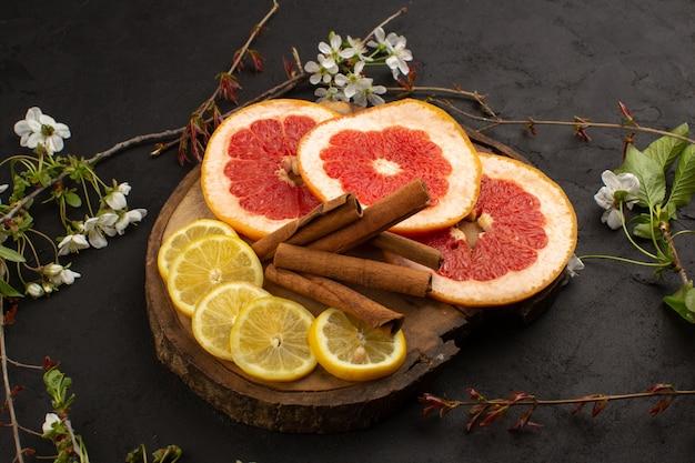 Bovenaanzicht gesneden grapefruits citroenen samen met kaneel op de grijze vloer