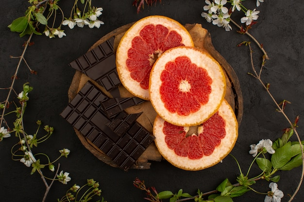 Bovenaanzicht gesneden grapefruits en choco bars op de donkere vloer