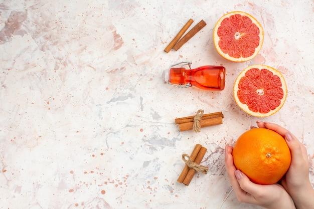 Bovenaanzicht gesneden grapefruits kaneelstokjes fles grapefruit in vrouwelijke hand op naakt oppervlak vrije ruimte