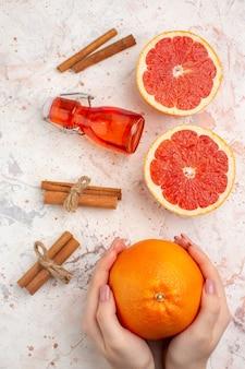 Bovenaanzicht gesneden grapefruits kaneelstokjes fles grapefruit in vrouwelijke hand op naakt oppervlak