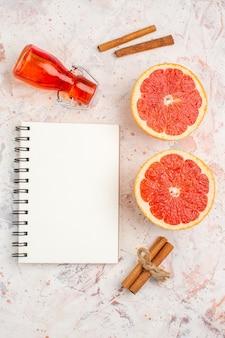 Bovenaanzicht gesneden grapefruits kaneelstokjes fles kladblok op naakt oppervlak