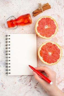 Bovenaanzicht gesneden grapefruits kaneelstokjes fles kladblok rode marker in vrouwelijke hand op naakt oppervlak