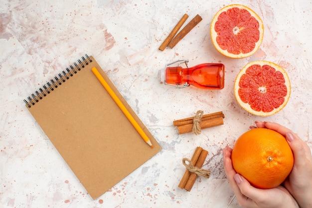 Bovenaanzicht gesneden grapefruits kaneelstokjes fles notebook geel potlood grapefruit in vrouwelijke hand op naakt oppervlak