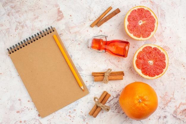 Bovenaanzicht gesneden grapefruits kaneelstokjes fles notebook geel potlood op naakt oppervlak