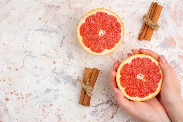 Bovenaanzicht gesneden grapefruits kaneelstokjes gesneden grapefruit in vrouwelijke hand op naakt oppervlak vrije ruimte