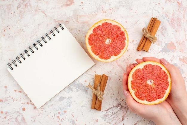 Bovenaanzicht gesneden grapefruits kaneelstokjes notebook gesneden grapefruit in vrouwelijke hand op naakt oppervlak