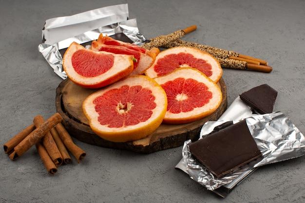 Bovenaanzicht gesneden grapefruits langs kaneel en choco bars op de grijze achtergrond
