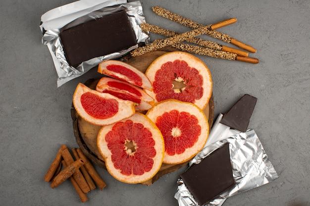 Bovenaanzicht gesneden grapefruits met choco bar en kaneel op de grijze achtergrond