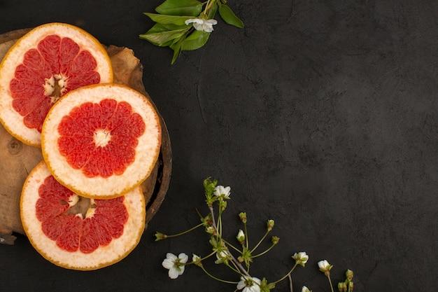 Bovenaanzicht gesneden grapefruits ringen zacht sappig op de donkere achtergrond
