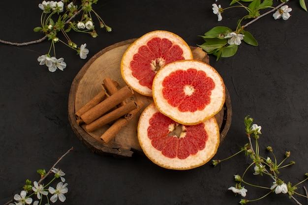 Bovenaanzicht gesneden grapefruits sappig samen met kaneel op de donkere vloer