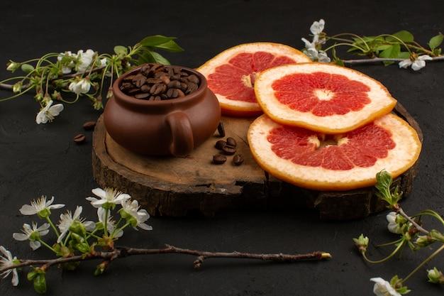 Bovenaanzicht gesneden grapefruits vers rijp sappig zacht samen met koffie bruine zaden op de donkere vloer
