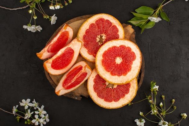 Bovenaanzicht gesneden grapefruits verse zachte sappig op het bruine bureau en de donkere achtergrond